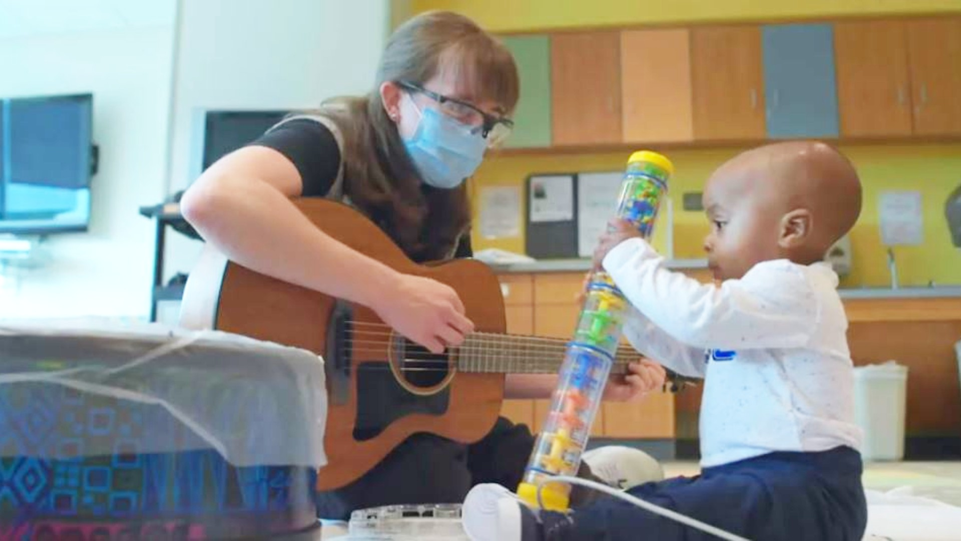 A music therapist plays guitar with a young Levine Children's Hospital patient.